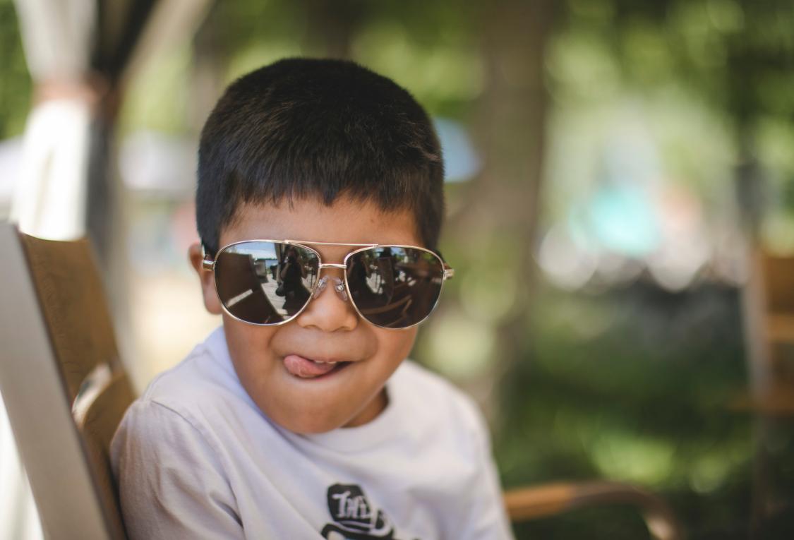 un petit garçon portant des lunettes de soleil qui fait une grimace