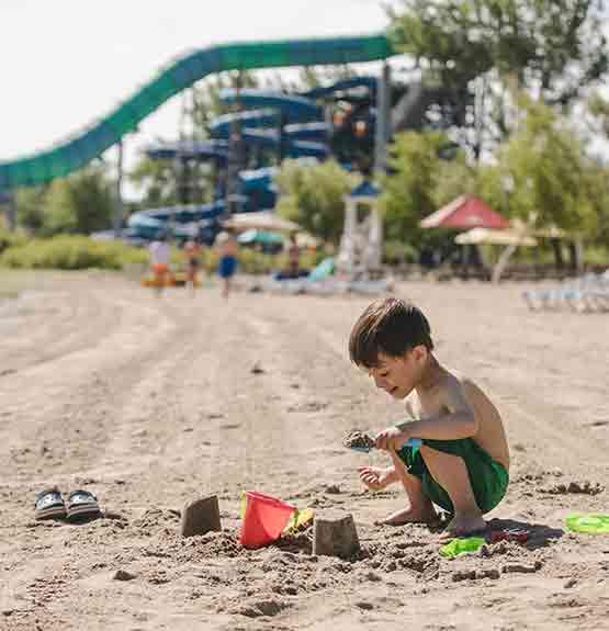 enfant qui joue avec sceau et sable sur une plage avec glissades derrière