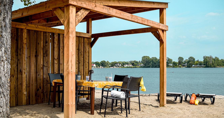 Plage sur lac avec chaises longues, table, chaises et auvent