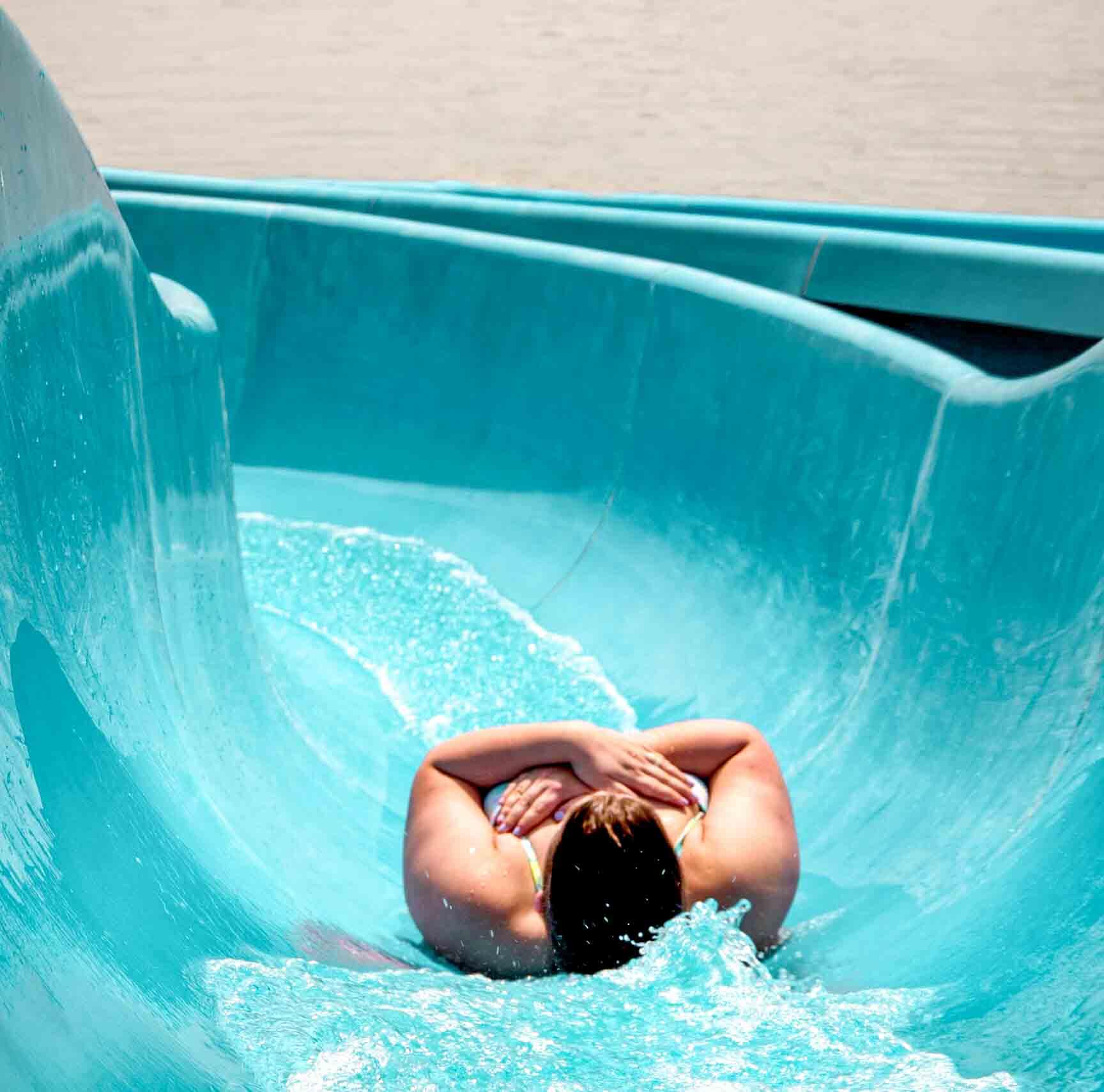 femme glissant dans une glissade bleue vers le lac