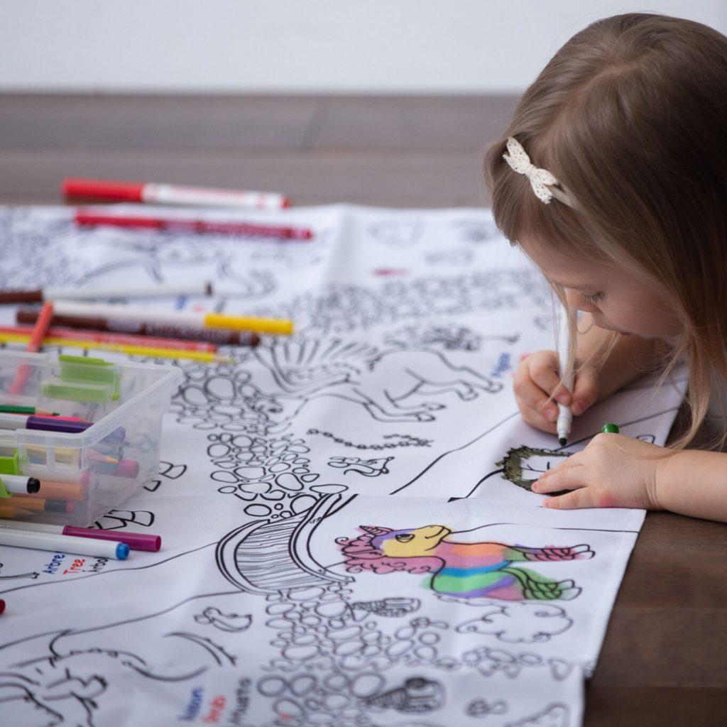 petite fille qui colore une nappe