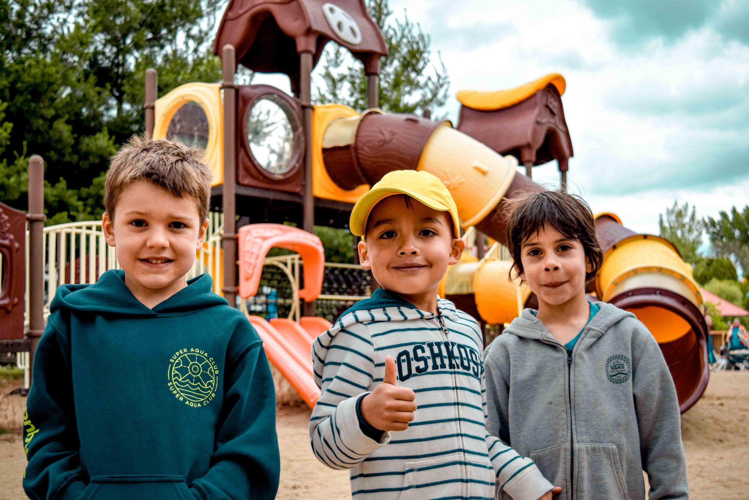 trois enfants devant module de jeux secs