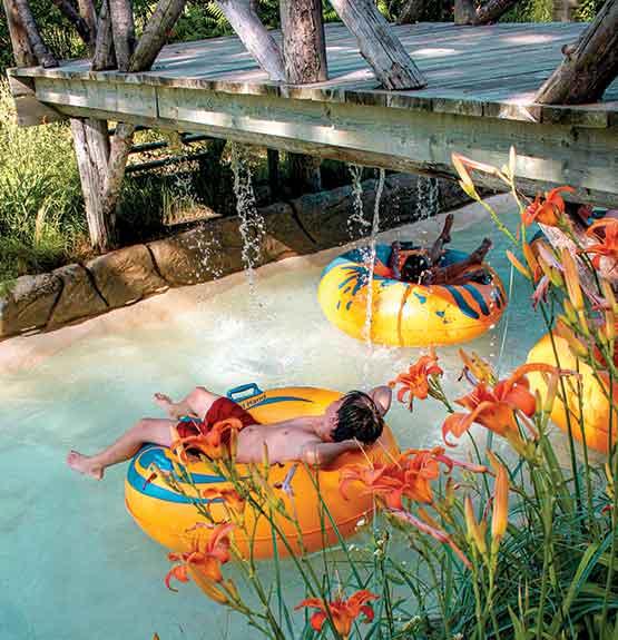 Enfants dans tubes jaune et bleu dans rivière avec pont