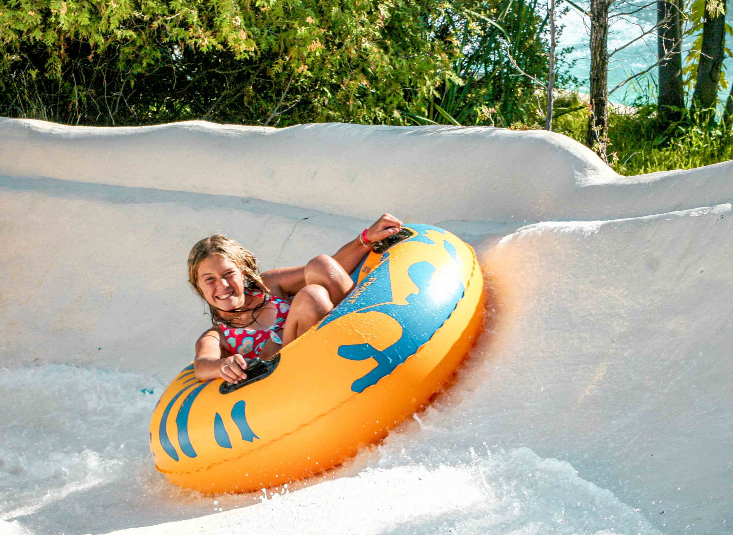 Enfant glissant dans un tube jaune dans une glissade blanche, la Nouvelle Rivière Sauvage