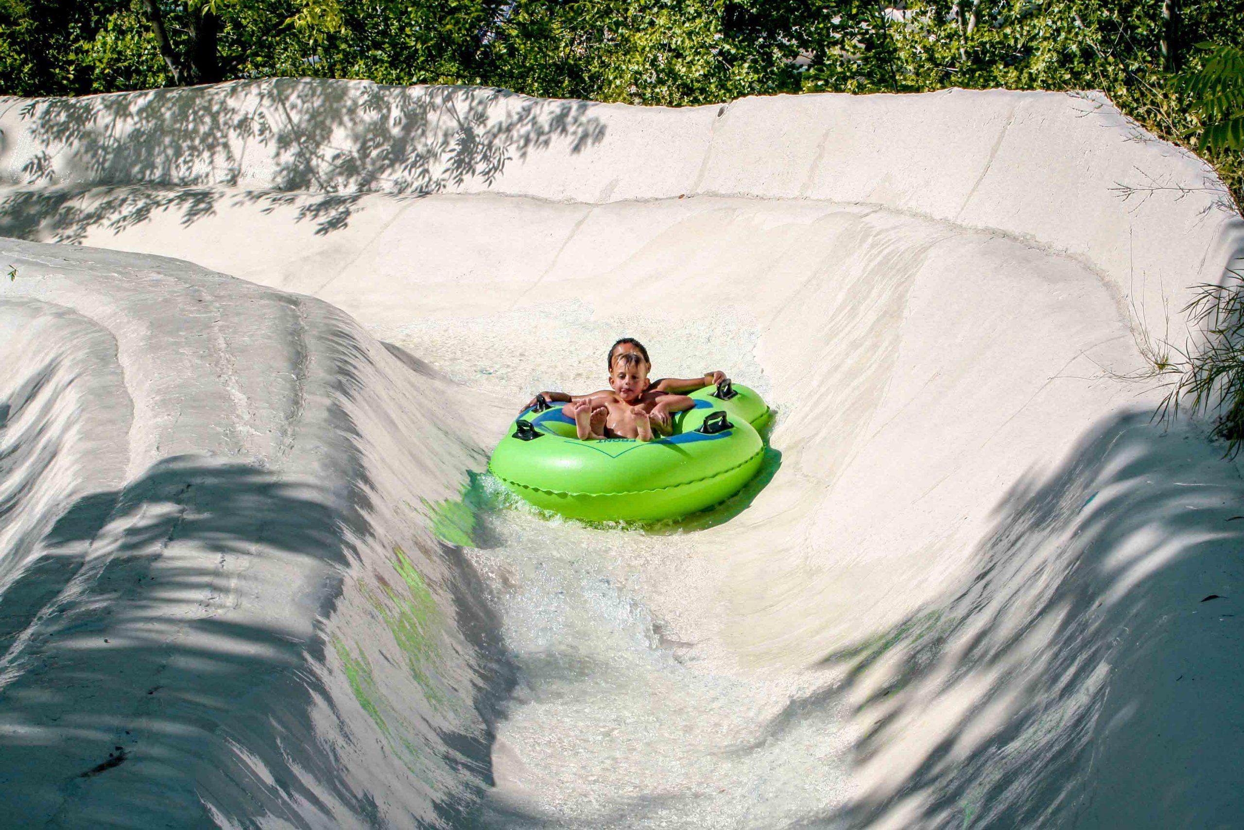enfants sur tube vert dans une glissade blanche