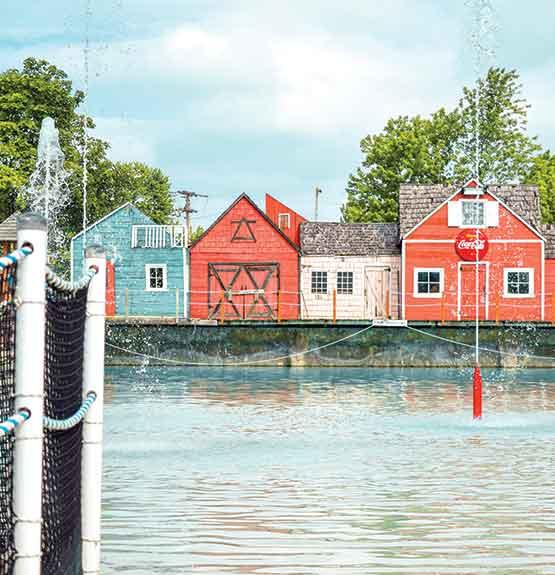 Grand bassin d'eau avec jets, maisons et clotures