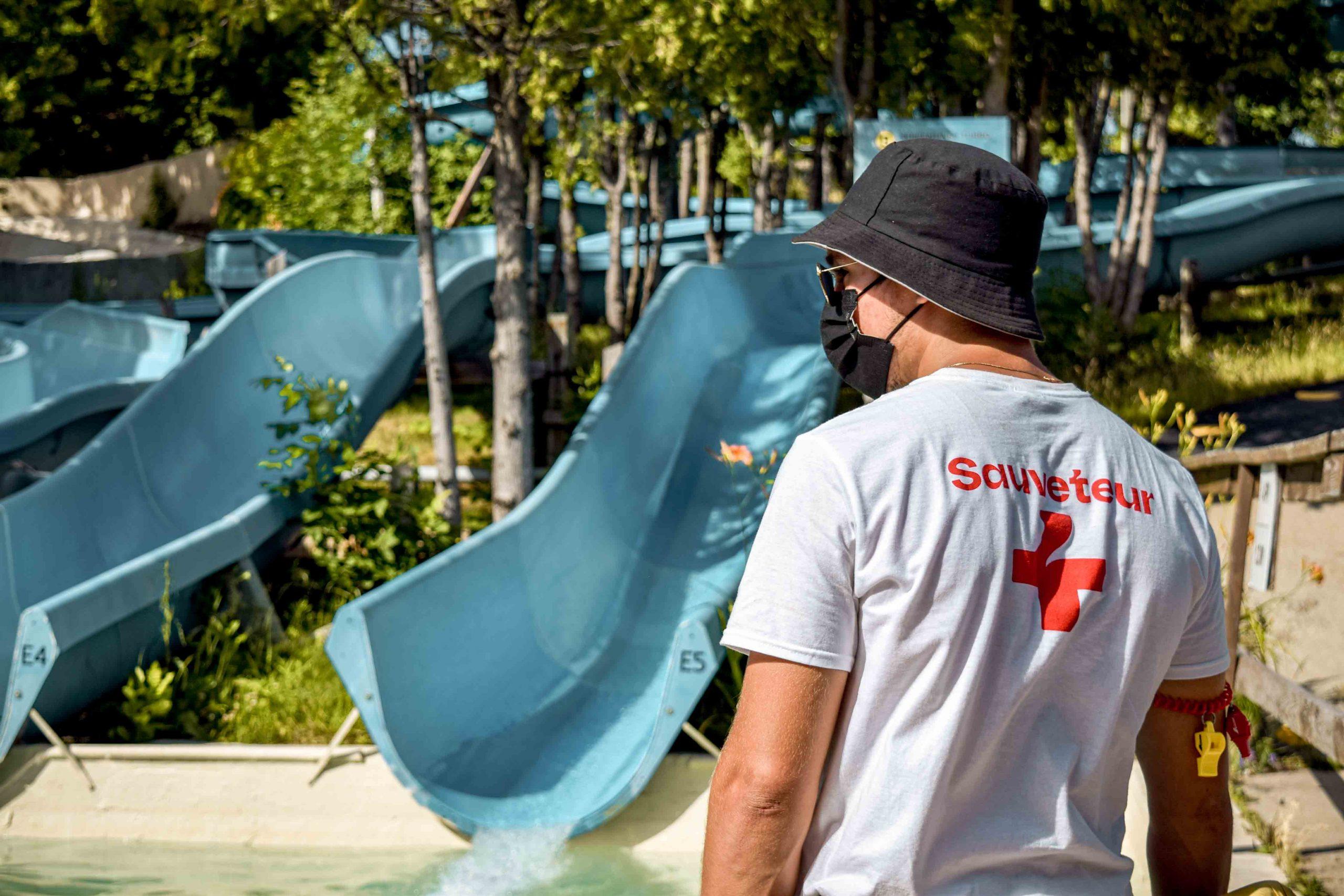 Sauveteur devant glissades bleues, les Twisters et arbres